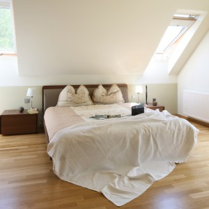 Przyroda wkradająca się do sypialni przez okna oraz podłoga z drewna nadają wnętrzu subtelny, naturalny wygląd sprzyjający odpoczynkowi. Jasną aranżację delikatnie przełamują brązowe meble. Projekt: Agnieszka Lorenc. Fot. Bartosz Jarosz.