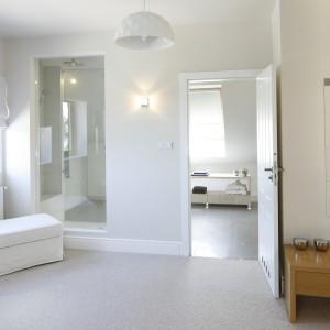 Z sypialnią sąsiaduje łazienka przeznaczona wyłącznie dla gospodarzy. Przeszklenie w ścianie między pokojem a strefą prysznica, dodaje spokojnej aranżacji ekstrawagancji. Projekt: Kamila Paszkiewicz. Fot. Bartosz Jarosz.