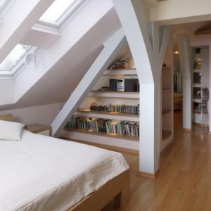W sypialni znajduje się też biblioteczka oraz gabinet z wygodnym fotelem. Poszczególne strefy naturalnie rozgraniczają elementy konstrukcyjne poddasza. Projekt: Barbara Gryt. Fot. Monika Filipiuk-Obałek.