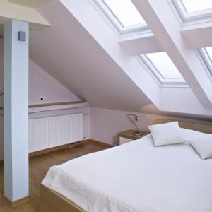 W białej sypialni na poddaszu łóżko ustawiono pod oknami dachowymi, dzięki czemu przed snem można obserwować spadające gwiazdy. Projekt: Barbara Gryt. Fot. Monika Filipiuk-Obałek.