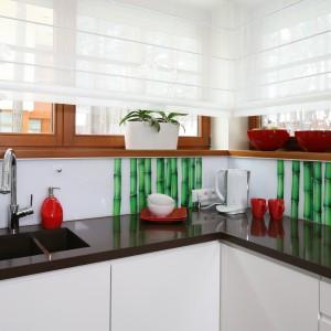 Ścianę nad blatem zdobi fototapeta z orzeźwiającym motywem zielonych bambusów, przekryta dla bezpieczeństwa szkłem. Z mocną zielenią pięknie kontrastują czerwone dodatki. Projekt: Katarzyna Mikulska-Sękalska. Fot. Bartosz Jarosz.