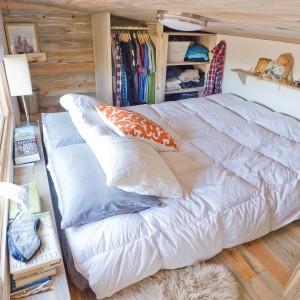 Sypialnia jest zaskakująco komfortowa. Oprócz sporego, dwuosobowego łóżka, wpasowano tutaj również półki i szafkę z wieszakami na ubrania. Za wezgłowiem łóżka znalazło się nawet miejsce na pociągniętą przez całą długość pomieszczenia półkę nocną na lampy i książki. Projekt i zdjęcia: Alek Lisefski.
