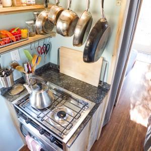 W rogu kuchni urządzono przestrzeń gotowania. Znalazła się tutaj płyta grzejna, piekarnik w zabudowie oraz akcesoria kuchenne, wiszące nad blatem. Projekt i zdjęcia: Alek Lisefski.