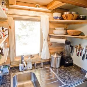 Dzięki obecności dwóch okien, kuchnia jest rozświetlana naturalnym światłem i nie przeraża ciasnotą, mimo licznych sprzętów i półek, sięgających aż do samego sufitu. Projekt i zdjęcia: Alek Lisefski.