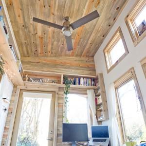 Duża ilość wysokich okien i dodatkowych doświetlających świetlików pod sufitem sprawia, że mały domek nie przeraża klaustrofobicznym klimatem, a wręcz jest bardzo przyjemny w odbiorze. Projekt i zdjęcia: Alek Lisefski.