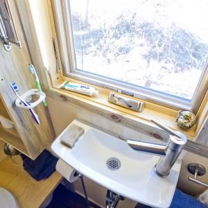 Parapet przy umywalce wykorzystano na dodatkową półkę, na której można położyć podręczne akcesoria łazienkowe. Projekt i zdjęcia: Alek Lisefski.