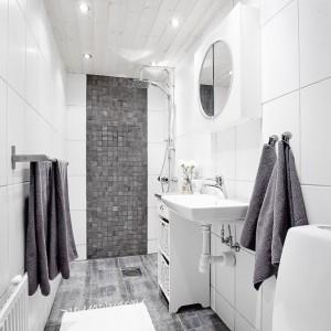 Biel łazienki przełamano szarymi płytkami w dwóch odcieniach. Ciemniejsze znajdziemy na ścianie za wc oraz w strefie prysznica, jaśniejsze ułożono na podłodze. Fot. Vastanhem.