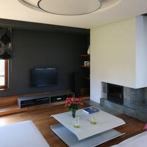 W urządzonym w minimalistycznym stylu salonie dominują naturalne materiały. Telewizor doskonale wtopił się w czerń ściany. Projekt: Magdalena Konopko, Marcin Konopko. Fot. Bartosz Jarosz.