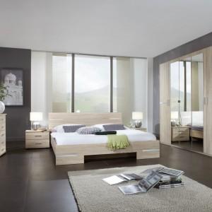 Sypialnia Anna Abra Meblew kolorze dąb sonoma z chromowanymi, pobłyskującymi dodatkami. Zaletą tej sypialni jest wyjątkowo duża szafa z pięcioma otwierającymi się drzwiami i lustrem umocowanym na całej jej wysokości. Fot. Abra Meble.