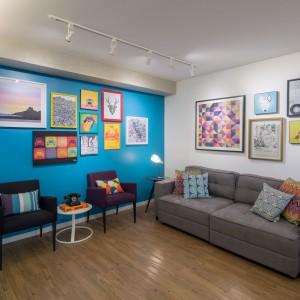 Ścianę w salonie pomalowano na energetyzujący kolor turkusowy. Udekorowano ją kolorowymi grafikami, które razem z tłem wprowadzają wakacyjną atmosferę. Projekt: Semerene Arquitetura Interior. Fot. Joana França