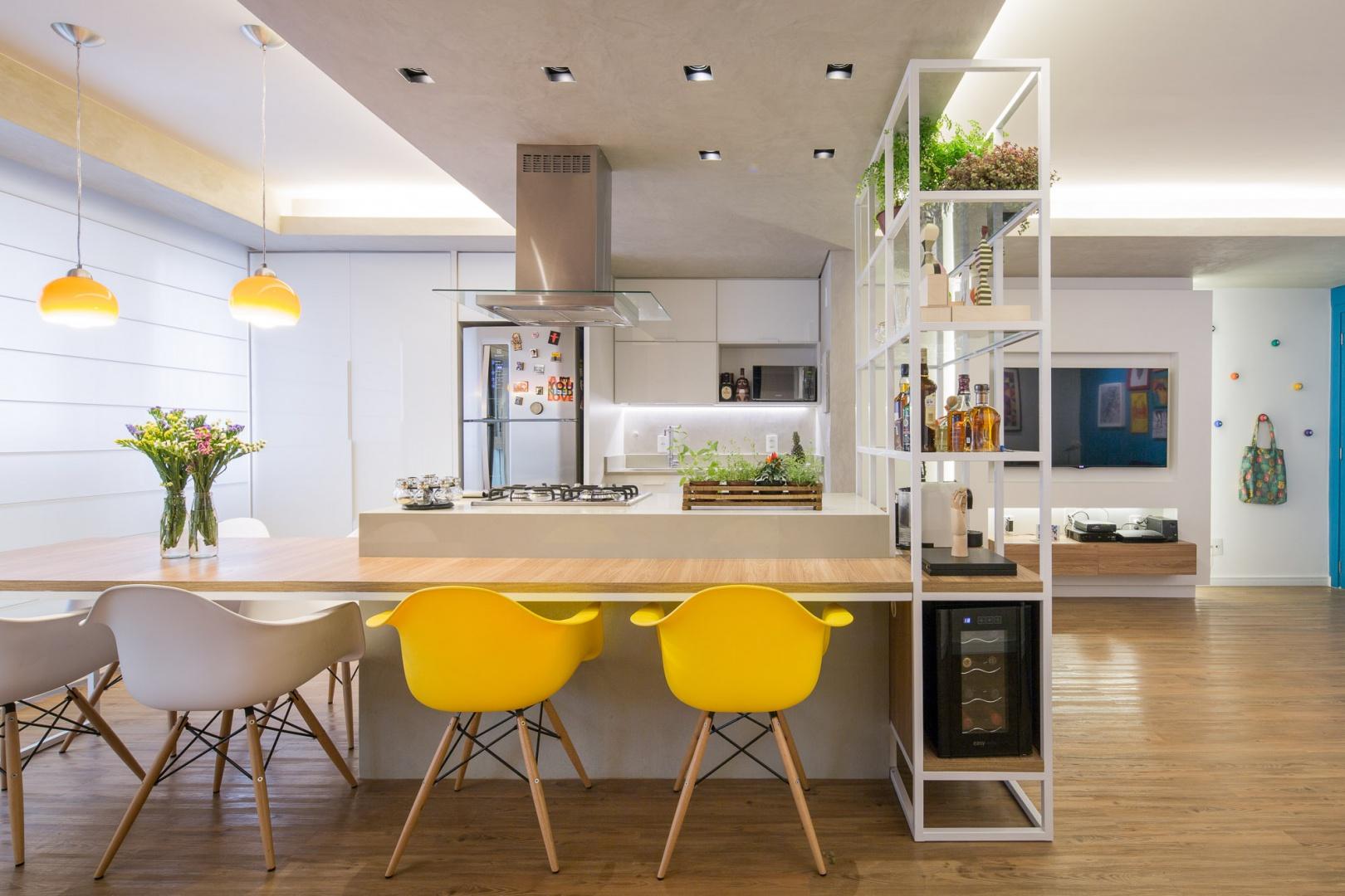 Centralnym punktem całego mieszkania jest wyspa, połączono ze stołem jadalnianym na 6 osób. Projekt: Semerene Arquitetura Interior. Fot. Joana França.