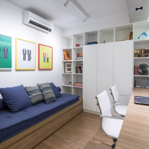 W gabinecie kontynuowany jest motyw geometrycznych, białych elementów - tym razem już nie w formie metalowych prętów, ale pojemnej szafy. Projekt: Semerene Arquitetura Interior. Fot. Joana França.