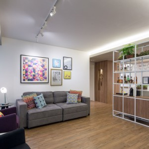 """Salon od kuchni oddziela przezierna """"ścianka"""", uformowana z pomalowanych na biało metalowych prętów. Element służy również za regał z licznymi półkami. Projekt: Semerene Arquitetura Interior. Fot. Joana França."""