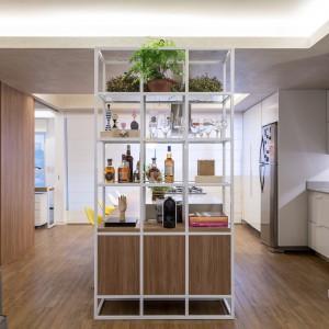 Metalowe pręty, służące za półki i element działowy wprowadzają do wnętrza delikatnie industrialny klimat. Projekt: Semerene Arquitetura Interior. Fot. Joana França.