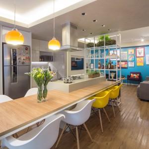 Bazą aranżacyjną w mieszkaniu są neutralne materiały, jak drewno i beton. Ożywiono je kolorowymi dodatkami, np. w postaci żółtych krzeseł i lamp. Projekt: Semerene Arquitetura Interior. Fot. Joana França.