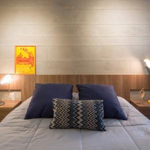 W sypialni panuje delikatnie industrialna atmosfera, którą buduje ściana nad wezgłowiem łóżka. Ocieplającym elementem jest drewniany panel, będący tłem dla mebla. Projekt: Semerene Arquitetura Interior. Fot. Joana França.