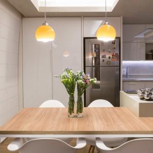 Funkcje gospodarcze, takie jak pralnia, estetycznie schowano za białą zabudową w kuchni. Projekt: Semerene Arquitetura Interior. Fot. Joana França.