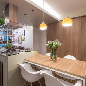 Gabinet chowa się za przesuwnymi drzwiami, które zamknięte wyglądają jak pokryta fornirem ściana, a otwarte odkrywają kolejne pomieszczenie. Projekt: Semerene Arquitetura Interior. Fot. Joana França.