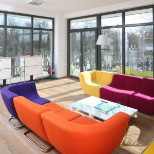 Przestronny salon zdobią nie tylko duże przeszklenia, ale też kolorowe sofy modułowe, których konfiguracje można dowolnie zmieniać. Projekt: Konrad Grodziński. Fot. Bartosz Jarosz.