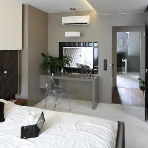 W sypialni dominuje odcień szarości wpadający w brąz, przez co nowoczesne wnętrze jest niezwykle przyjemne w odbiorze. Geometryczne formy oraz połyskujące powierzchnie nadają przestrzeni glamourowy styl. Projekt: Chantal Springer. Fot. Bartosz Jarosz.