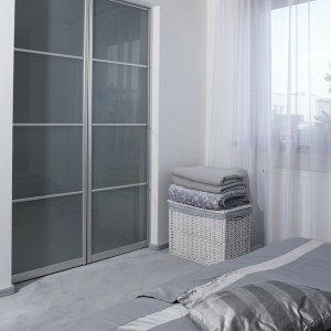 Praktycznym rozwiązaniem jest garderoba, do której prowadzą drzwi z szarego szkła. Projekt: Piotr Wełniak. Fot. Monika Filipiuk-Obałek.