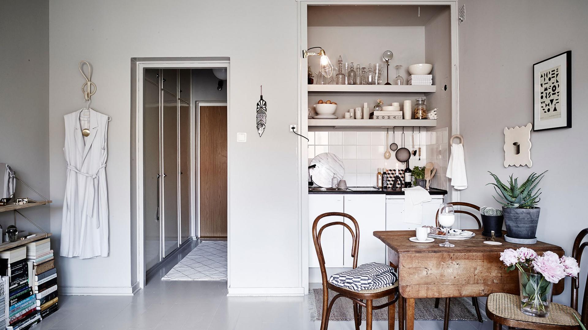 Niewielki aneks kuchenny symbolicznie od reszty pomieszczenia oddziela mały stół jadalniany dla trzech osób. Ciemny, przytulny kolor drewna ociepla wizualnie chłodne szarości dominujące we wnętrzu. Fot. Stadshem.