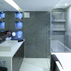 Pod umywalką umieszczono szafkę, w której udało się ukryć pralkę. Dodatkowo znajdziemy w niej wiele praktycznych schowków. Obok kabiny prysznicowej i nad szafką z umywalką zaplanowano otwarte półki. Projekt: Agnieszka Hajdas-Obajtek. Fot. Bartosz Jarosz.