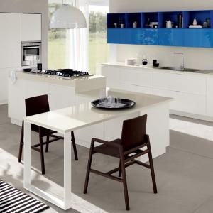 Białą, elegancką kuchnię ożywia mocny akcent kolorystyczny w postaci górnych szafek wykończonych w intensywnym odcieniu niebieskiego, wpadającego w granat. Tak urządzona kuchnia z pewnością wprowadzi domowników w dobry nastrój. Fot. Scavolini, model Mood.