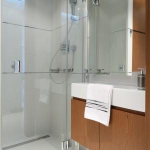 Białą łazienkę ocieplają drewniane meble wykonane na zamówienie. Dzieki nim wnętrze staje się bardziej przytulne. Projekt: Anna Maria Sokołowska. Fot. Bartosz Jarosz.