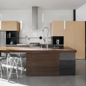 Na parterze domu usytuowano bardzo dużą, nowoczesną, rozświetloną światłem dziennym kuchnię. Jej punkt centralny stanowi obszerna wyspa. Projekt: Natalie Dionne Architecte. Fot. Marc Cramer.