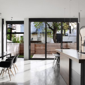W strefie kuchni i jadalni panuje czysty wystrój. Białe ścianie idealnie harmonizują z szarymi i czarnymi meblami, a proste formy i gładkie powierzchnie dopełniają całości. Projekt: Natalie Dionne Architecte. Fot. Marc Cramer.
