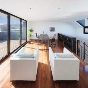 Na ostatnim piętrze w sąsiedztwie klatki schodowej po jednej stronie i tarasu po drugiej, usytuowano elegancki kącik wypoczynkowy. Projekt: Natalie Dionne Architecte. Fot. Marc Cramer.