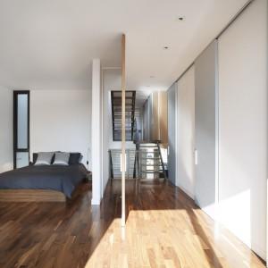 Brak tradycyjnego podziału przestrzeni optycznie powiększa wnętrze. Sypialnie znajdują się w bezpośrednim styku z ciągiem komunikacyjnym. Co jednak z uwagi na to, że każdy domownik ma swoje piętro, nie przeszkadza w odpoczynku. Projekt: Natalie Dionne Architecte. Fot. Marc Cramer.
