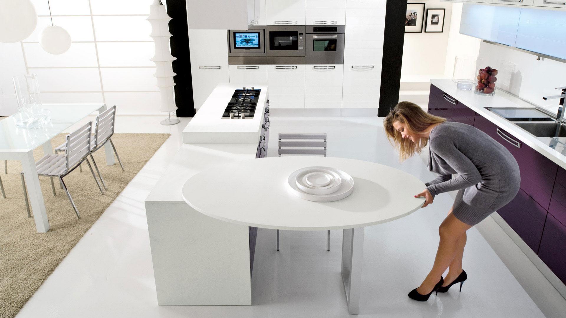 Kolorowa kuchnia, kształtem zbliżona do kwadratu, w wersji z ażurowym stolikiem. Jest bardzo funkcjonalna ponieważ ustawienie stolika można regulować. Fot. Lube Cucine