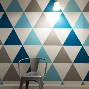 Chcąc urozmaicić wnętrze geometrycznymi wzorami, projektanci postanowili pomalować jedną ze ścian w niebiesko-szare trójkąty. Projekt: SHOKO.design. Fot. Małgorzata Opala.