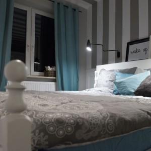 Dominujące w sypialni biel i szarości przełamano turkusowymi dodatkami w postaci zasłon w oknie i dekoracyjnych poduszek. Projekt: SHOKO.design. Fot. Małgorzata Opala.