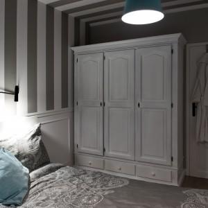 W sypialni postawiono na tapetę z pionowymi pasami, które jednak przechodzą również w poziom, wkraczając w powierzchnię sufitu, tworząc ciekawy efekt wizualny. Zabieg ten miał na celu nadanie pazura sypialni, bo właściciele nie chcieli, aby była nudna. Projekt: SHOKO.design. Fot. Małgorzata Opala.