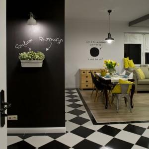 Ścianę przy wejściu do salonu pomalowano czarną farbą tablicową, która kolorystycznie idealnie harmonizuje z szachownicą na podłodze. Projekt: SHOKO.design. Fot. Małgorzata Opala.