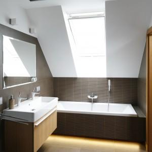 W łazience na poddaszu umieszczono delikatne oprawy oświetleniowe. Lampy dają wystarczającą ilość światła, a dzięki prostej formie doskonale komponują się z oszczędnym wystrojem łazienki. Projekt: Michał Mikołajczak. Fot. Bartosz Jarosz.