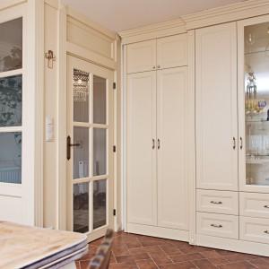 Niewielką ilość górnych szafek rekompensuje wysoka zabudowa poprowadzona aż pod sam sufit, wyposażona w liczne drzwiczki i szuflady. Charakterystycznym elementem są przeszklone witryny. Projekt i zdjęcia: Kamila Paszkiewicz.