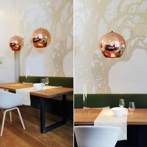 Złote detale nadają elegancki charakter strefie jadalni. Tutaj domownicy mogą wypocząć przy wspólnych posiłkach na wygodnej sofie, poprowadzonej przez całą długość ściany. Projekt: GAO Arhitekti. Fot. Mateja Jordovič Potočnik.