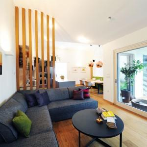 Salon otwiera się na dziedziniec, z którym łączą go duże, panoramiczne przeszklenia. Integracja wnętrza z otoczeniem powiększa je optycznie. Projekt: GAO Arhitekti. Fot. Mateja Jordovič Potočnik.