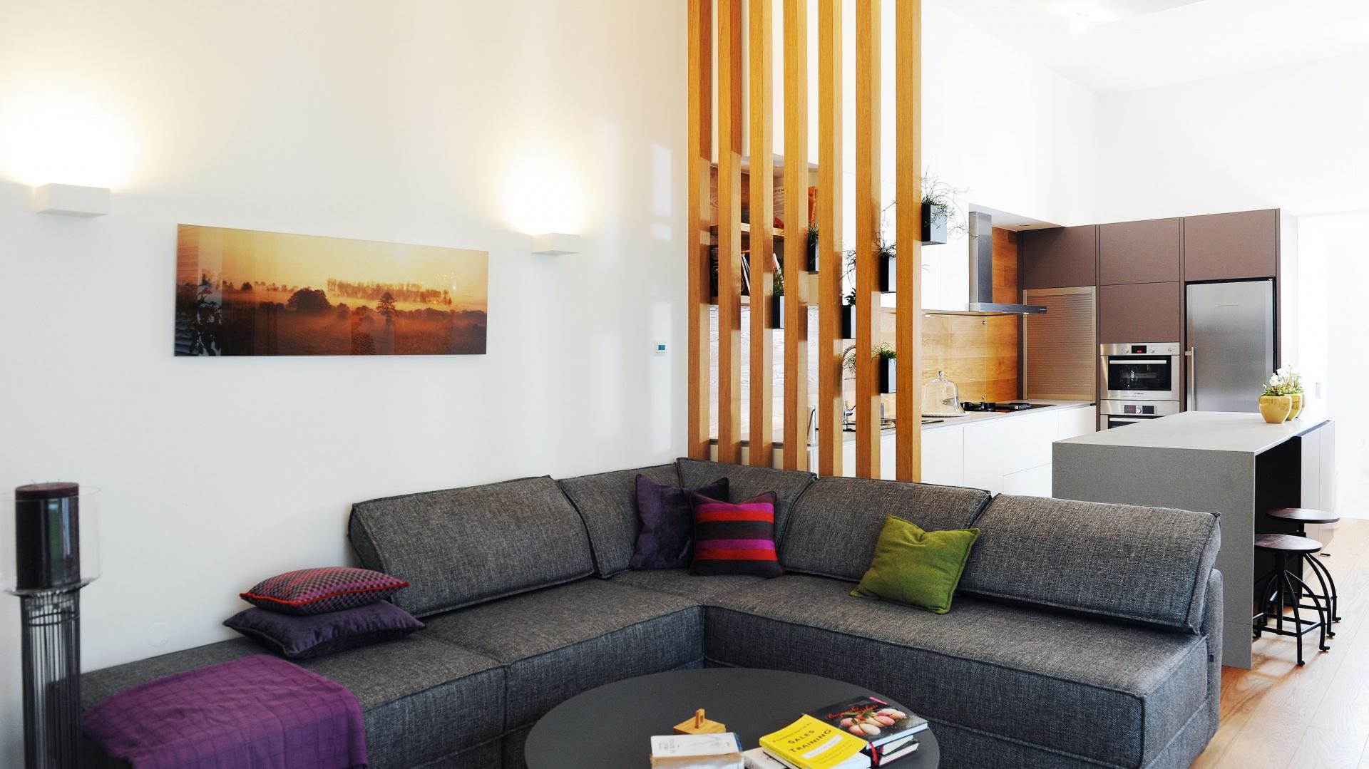 Strefę dzienną stanowi salon z jadalnią i kuchnią. Tę ostatnią od salonu oddziela oryginalne przepierzenie wykonane z dębowych desek. Przepuszcza ono światło i jest delikatnym detalem dekoracyjnym nie przytłaczającym przestrzeni. Projekt: GAO Arhitekti. Fot. Mateja Jordovič Potočnik.