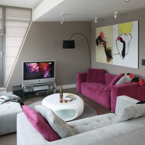 W kobiecym apartamencie nie mogło zabraknąć koloru. W salonie jest nim elegancki fiolet, w który ubrana została jedna z wygodnych sof. Projekt: Małgorzata Borzyszkowska. Fot. Bartosz Jarosz.