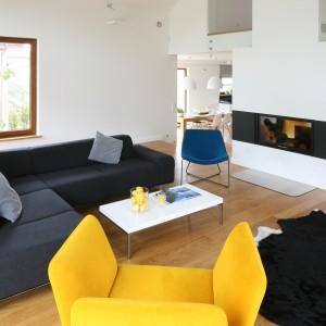 W przestronnym domu dominuje biel, która subtelnie łączy się z szarościami. Żółty fotel oraz niebieskie krzesło ożywiają stonowaną przestrzeń. Projekt: Małgorzata Galewska. Fot.  Bartosz Jarosz.