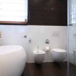W łazience zastosowano ponadczasowe zestawienie kolorów. Biel połączono z ciemną  podłogą oraz ciemnymi płytkami ściennymi, które pojawiają się na fragmentach dwóch ścian. Fot. Bartosz Jarosz.
