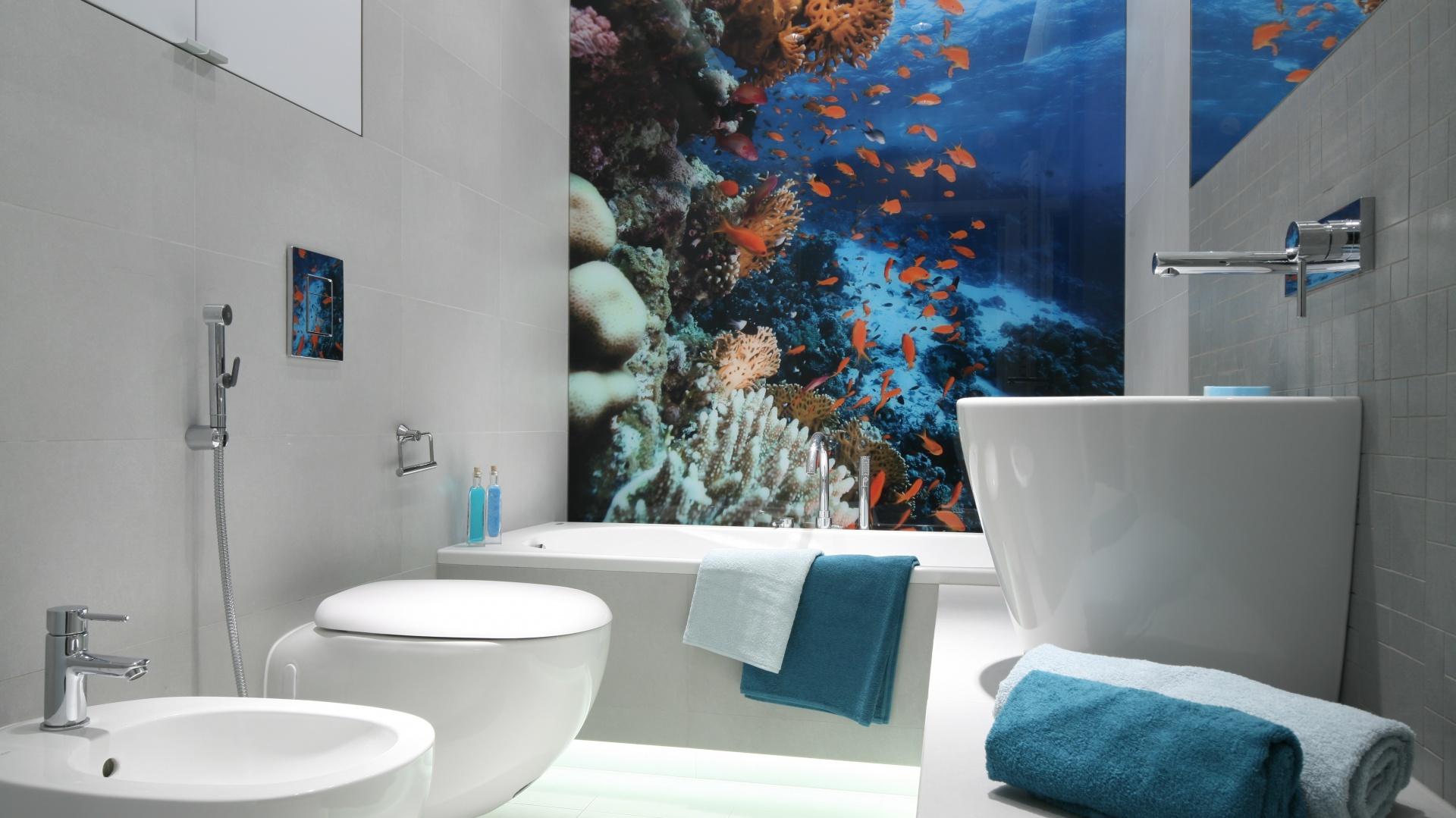 Tapeta z morskim motywem wprowadza do stonowanego wnętrza wiele koloru. Niebieski dobrze komponuje się z bielą ceramiki i delikatną szarością płytek. Projekt: Anna Maria Sokołowska. Fot. Bartosz Jarosz.