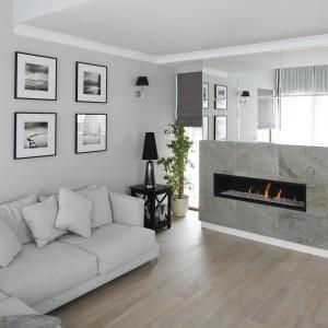 Przestronny salon urządzono w modnych szarościach. Ścianę z kominkiem zdobią tafle luster, które optycznie powiększają przestrzeń. Projekt: Magdalena Smyk. Fot. Bartosz Jarosz.