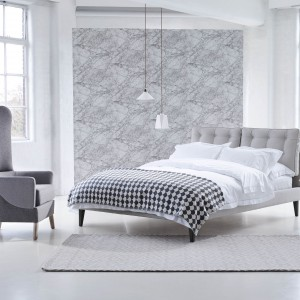 Wnętrze urządzone w szarościach nie musi być nudne i zimne. Aranżacja w tym modnym kolorze może być przytulna i bardzo gustowna. Wystarczy, że wykorzystamy w niej łóżko z tapicerowanym zagłówkiem, fotel o naturalnej formie, miękki dywan czy wzorzystą tapetę w jasnych, srebrzystych odcieniach. Fot. Heals.