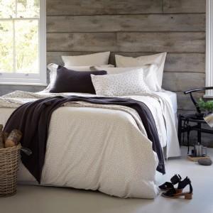 Modny, naturalny wygląd sypialni uzyskamy wykorzystując na ścianie nie tylko cegłę, ale i surowe drewno. Surowcem tym można wykończyć wszystkie ściany lub tylko jedną z nich. Fot. The Secret Linen Store.